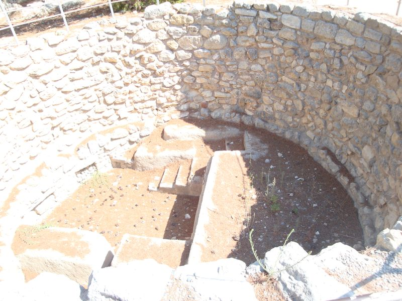 043. Well near entrance οf Knossos palace - One of three stone-lined pits about 5-6 meters in diameter and 3 meters deep. Evans assumed that they were built to quickly drain away surface water. Probably, the wells were used as storages for something or for sacrifice during religious ceremonies.
