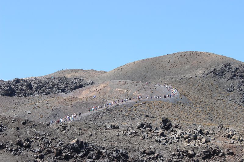 Line of tourists crawling along the bald mountain. Such an extraterrestrial scenery! Nea Kameni island, Santorini